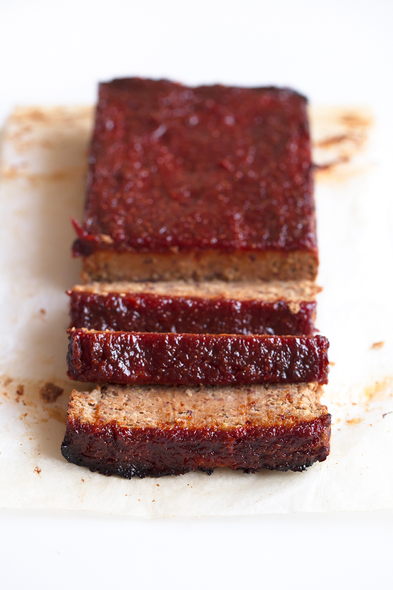 Foto de un pastel de carne vegano troceado sobre un fondo blanco