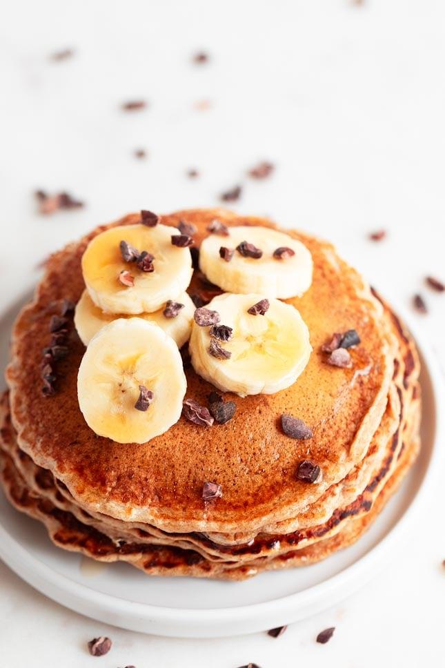 Foto desde arriba de un plato con pancakes veganos con plátano troceado y chips de chocolate