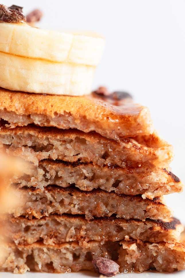Foto de cerca del corte de unos pancakes veganos con plátano y chips de chocolate