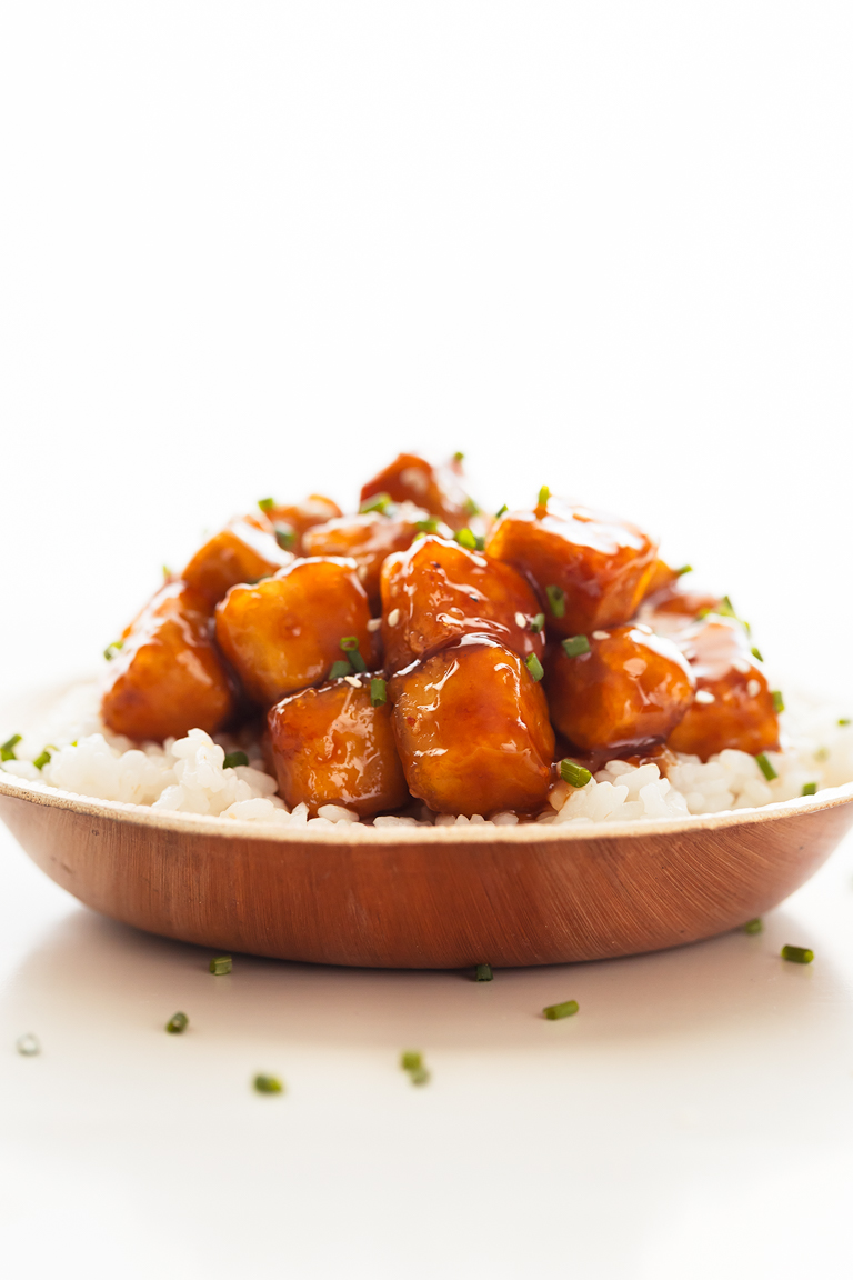 Foto de perfil de un plato con tofu General Tso servido sobre arroz blanco cocinado