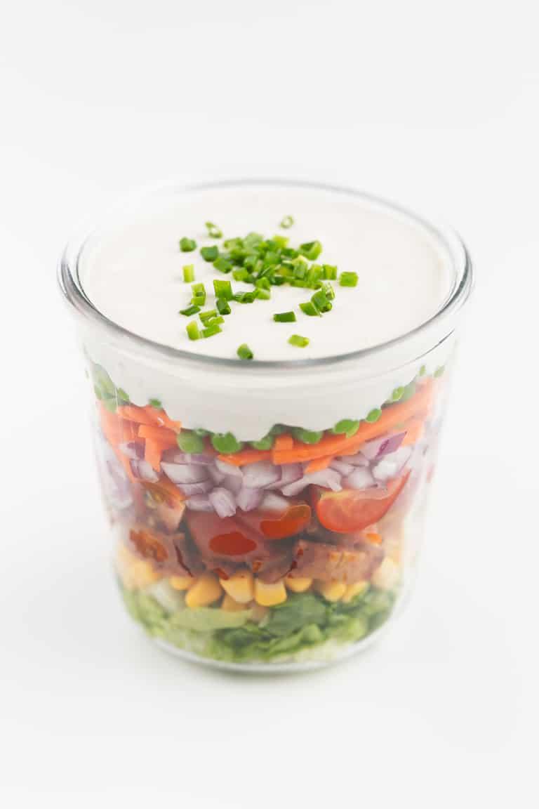 Ensalada de 7 Capas Vegana - Esta ensalada de 7 capas vegana es más sana que la original, pero está igual de rica. Lleva capas de vegetales, bacon de tempeh y un aliño muy cremoso. #vegano #singluten #danzadefogones