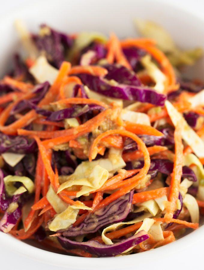 Ensalada de Col Vegana - Ensalada de col vegana, una versión vegetal y baja en grasa de la popular ensalada coleslaw. Nuestra receta lleva un aliño de aguacate en vez de mayonesa. #vegano #singluten #danzadefogones