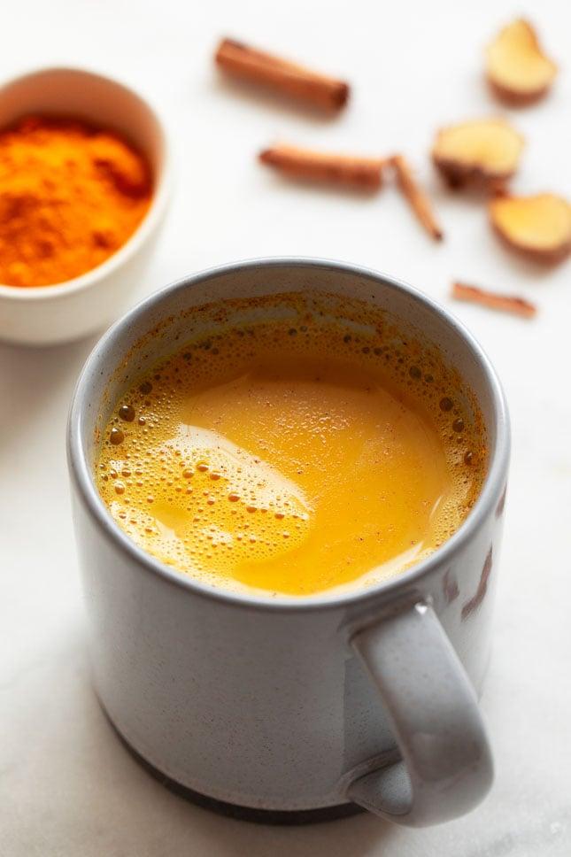 Foto de una taza de leche dorada decorada con canela y cúrcuma