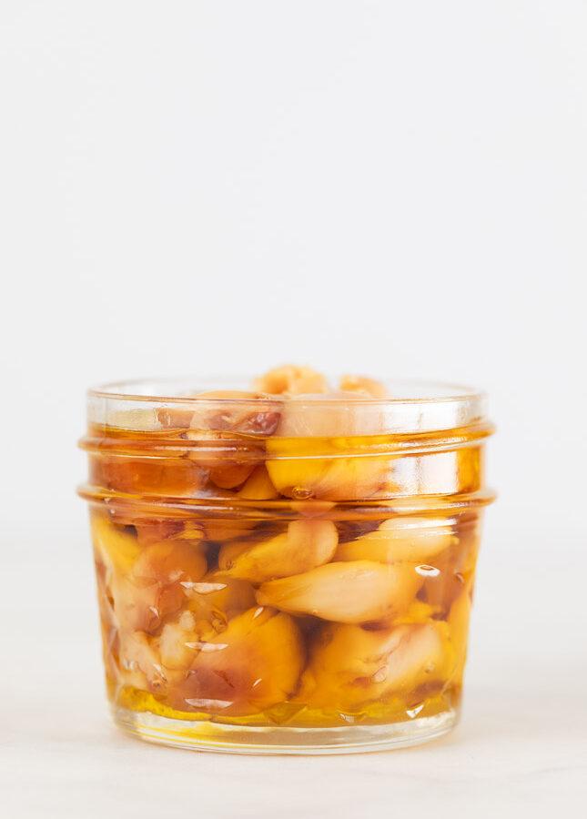Foto de perfil de un tarro de cristal con ajos asados en aceite