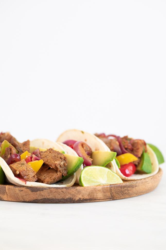 Foto de lado de un plato de madera con fajitas en tortillas