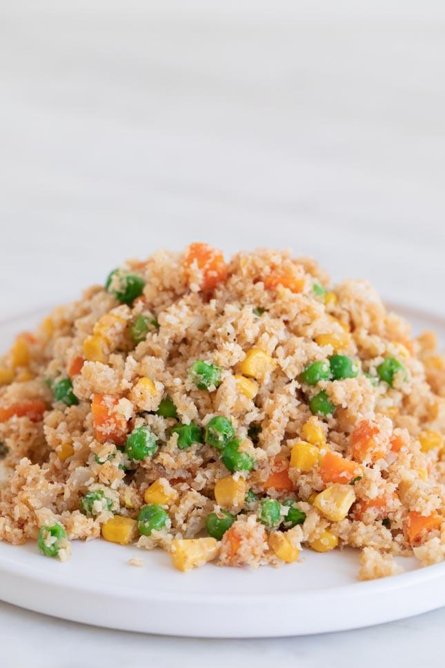 Foto de perfil de un plato blanco con arroz frito de coliflor casero