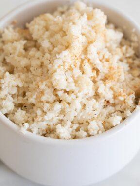 Foto de cerca de un bol pequeño con arroz de coliflor salteado dentro
