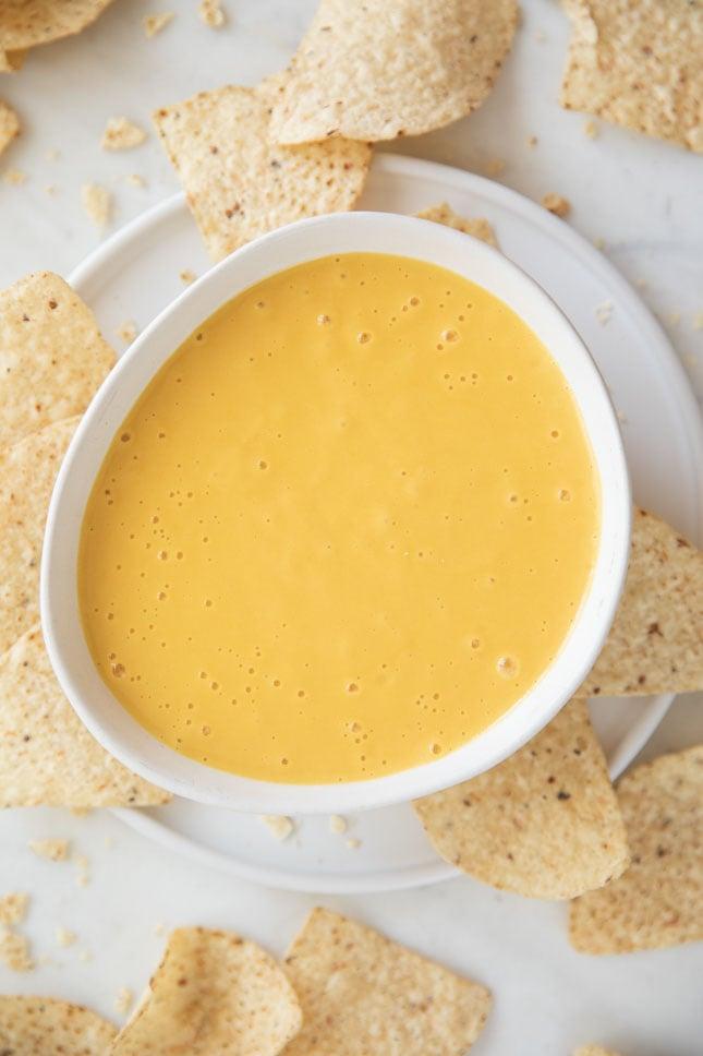 Foto desde arriba de un bol con queso vegano y nachos