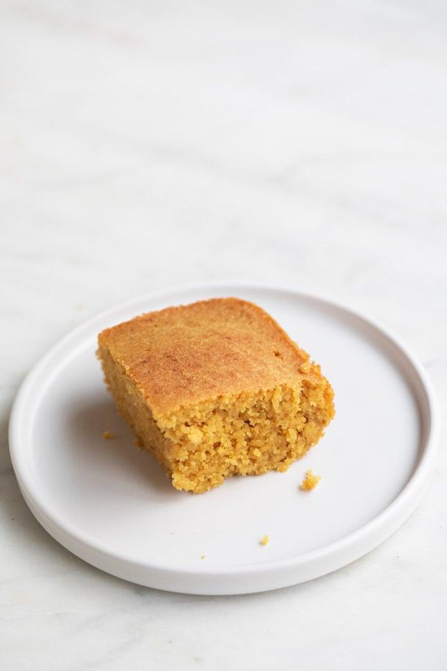Foto de un trozo de pan de maíz vegano sobre un plato blanco