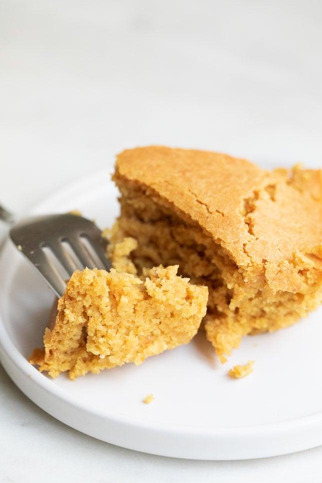 Foto de un trozo de pan de maíz vegano troceado en un plato con un tenedor
