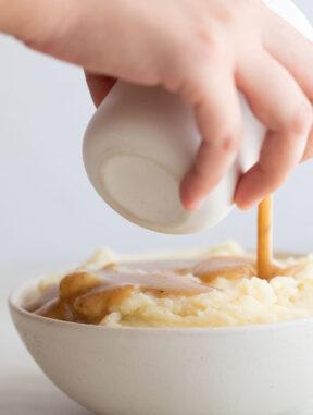 Foto de perfil de una mano echando salsa gravy vegana sobre un bol de puré de patatas