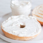 Foto cuadrada de un plato con un bagel untado con queso crema vegano