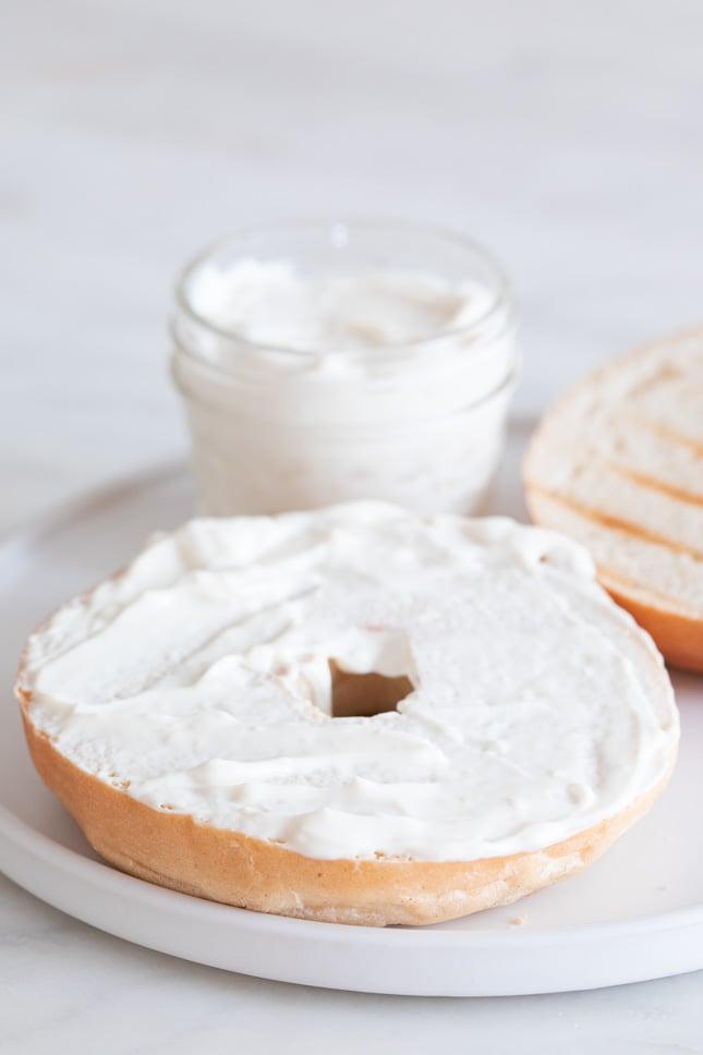 Foto de un bagel untado con queso crema vegano sobre un plato