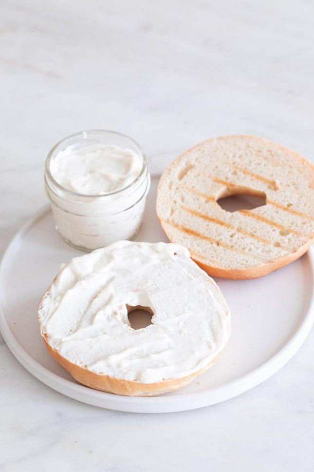 Foto de un plato con un tarro con queso crema vegano y un par de rebanadas de bagel untadas con queso