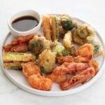 Foto pequeña de un plato con verduras en tempura y salsa de soja