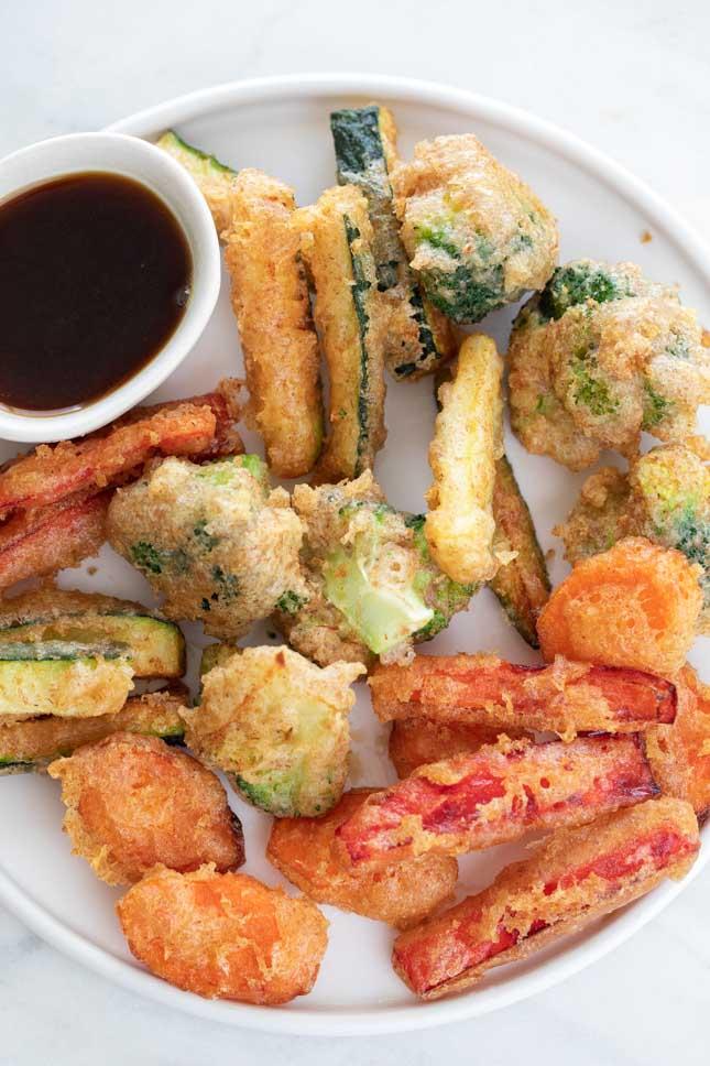 Foto desde arriba de un plato con un bol con salsa de soja y tempura de verduras