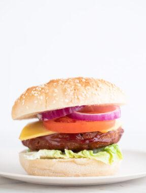 Foto de perfil de una hamburguesa vegana sobre un plato