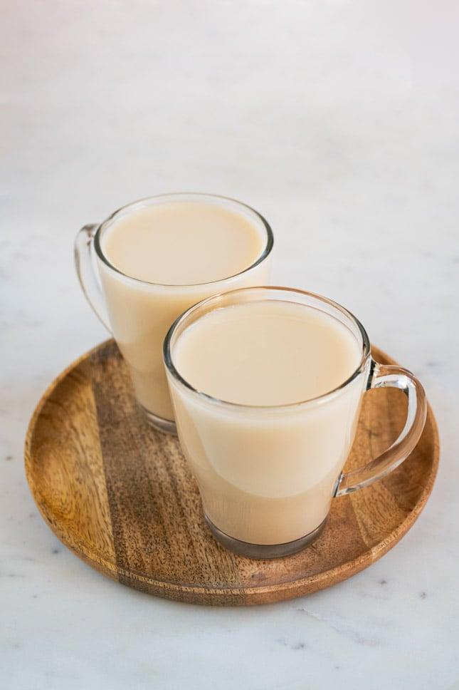 Foto de un par de tazas con leche de avena casera sobre una bandeja redonda de madera