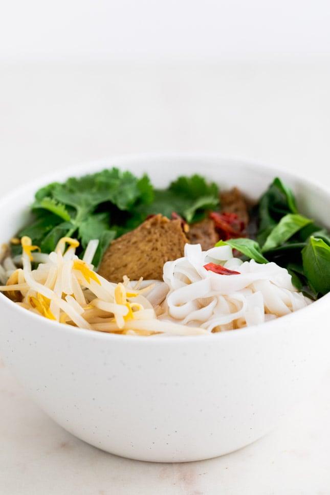 Foto de perfil de un bol con Pho vegano decorado con brotes de soja, seitán, noodles de arroz, cayena y hierbas