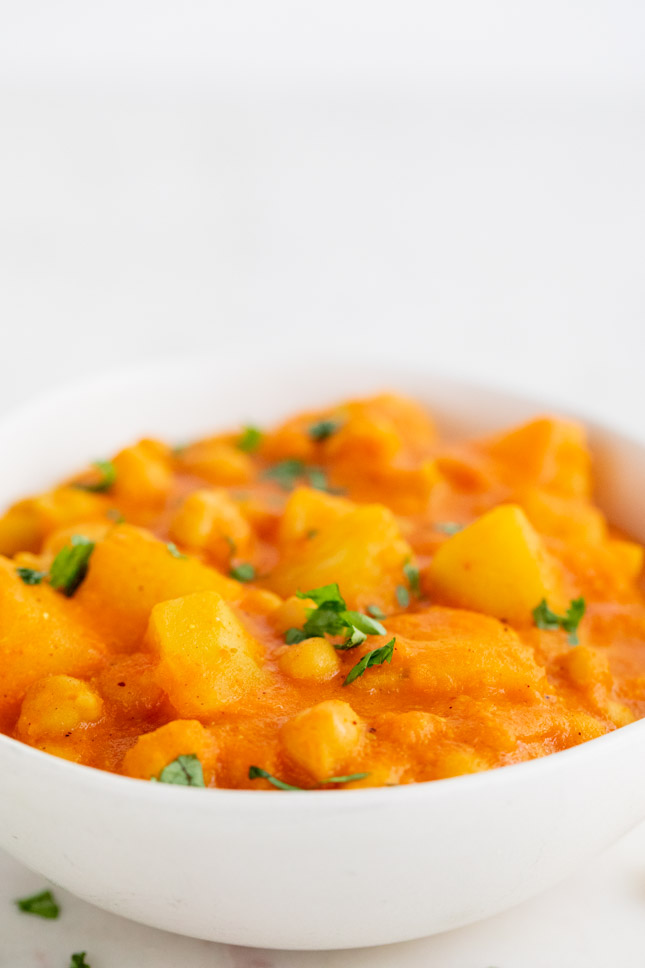 Foto de perfil de un bol con curry vegano con perejil fresco troceado por encima