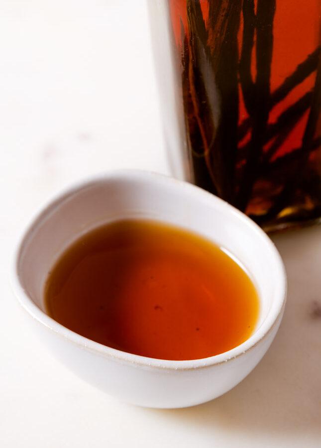 Foto de un cuenco pequeño y una botella de vidrio con extracto de vainilla casero