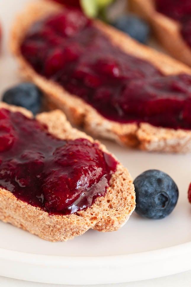 Foto de cerca de un plato con rebanadas de pan con compota de frutos rojos