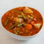 Foto cuadrada de un bol blanco con sopa de verduras