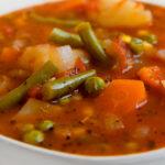 Foto de cerca de un bol con sopa de verduras con las palabras sopa de verduras