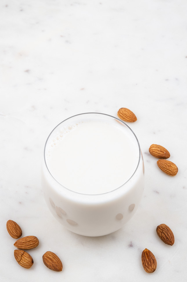 Foto de un vaso de leche de almendras con almendras de decoración alrededor