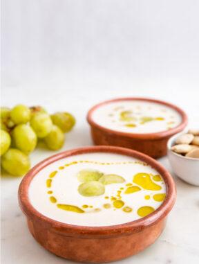 Foto de 2 bols de ajoblanco con decoración de uvas y aceite de oliva