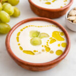 Foto cuadrada de un bol de ajoblanco decorado con uvas y aceite