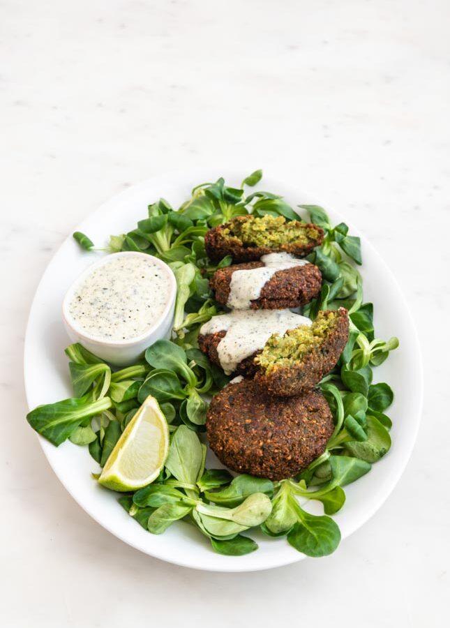 Foto de un plato de falafel con verduras y salsa de yogur vegana