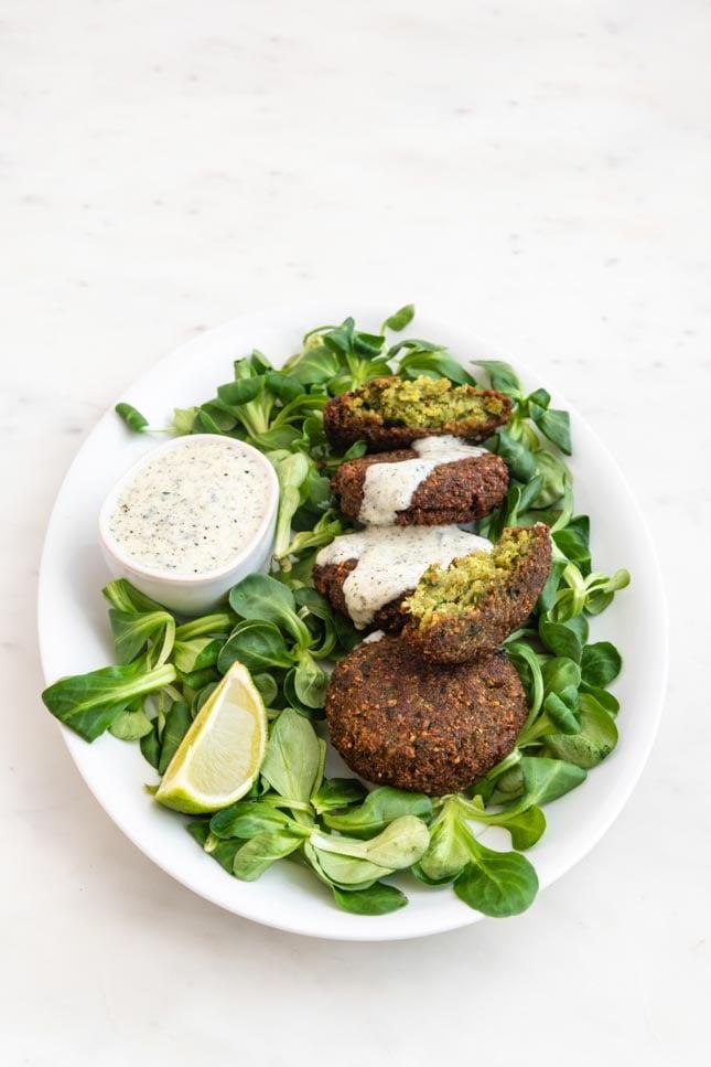 Foto de un plato con falafel decorado con verduras y salsa de yogur vegana