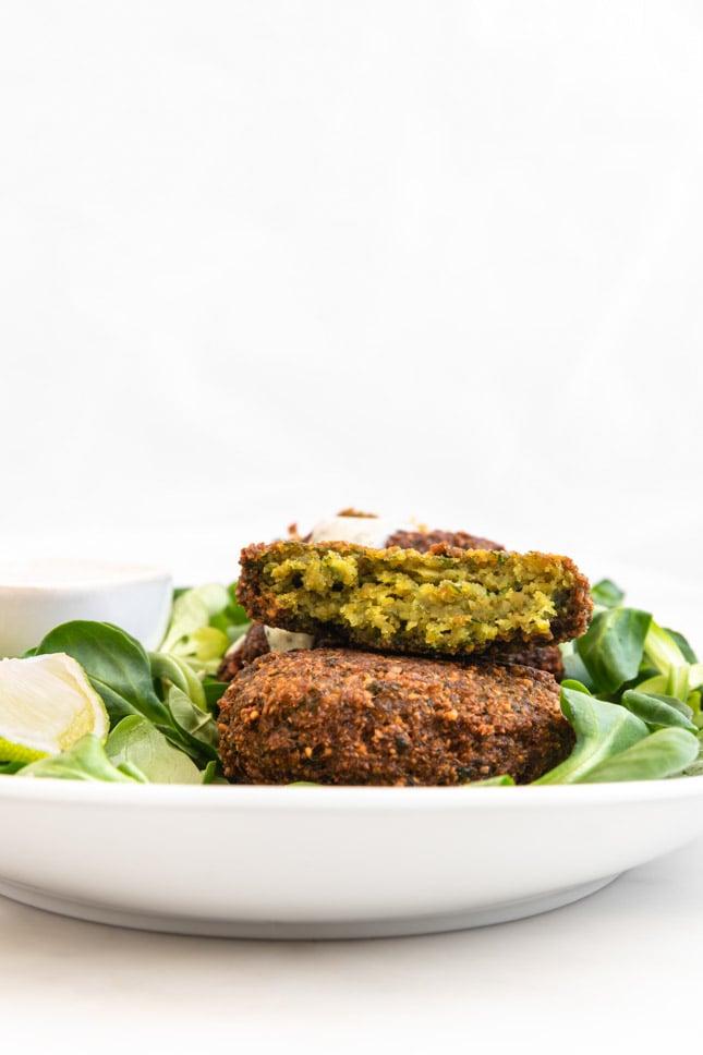 Foto de perfil de un plato con falafel decorado con verduras y salsa de yogur vegana