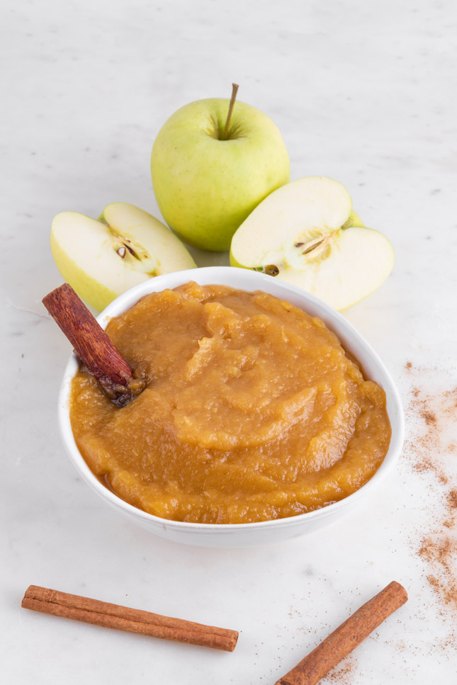 Foto de un bol de compota de manzana decorado con ramas de canela y manzana
