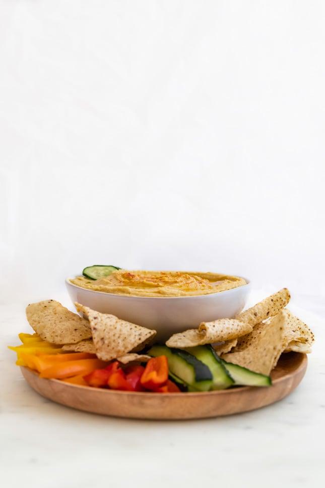 Foto de perfil de un bol de hummus con decoración de crudités