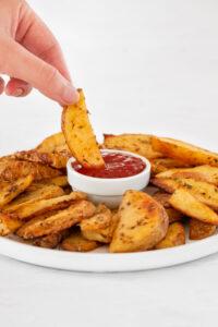 Foto de una mano cogiendo una de las patatas gajo